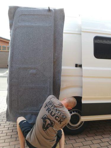 Adventure Truck Mitarbeiter beim Filzen der Hecktür eines Selbstausgebauten VW Crafter Campervan Filzverkleidung